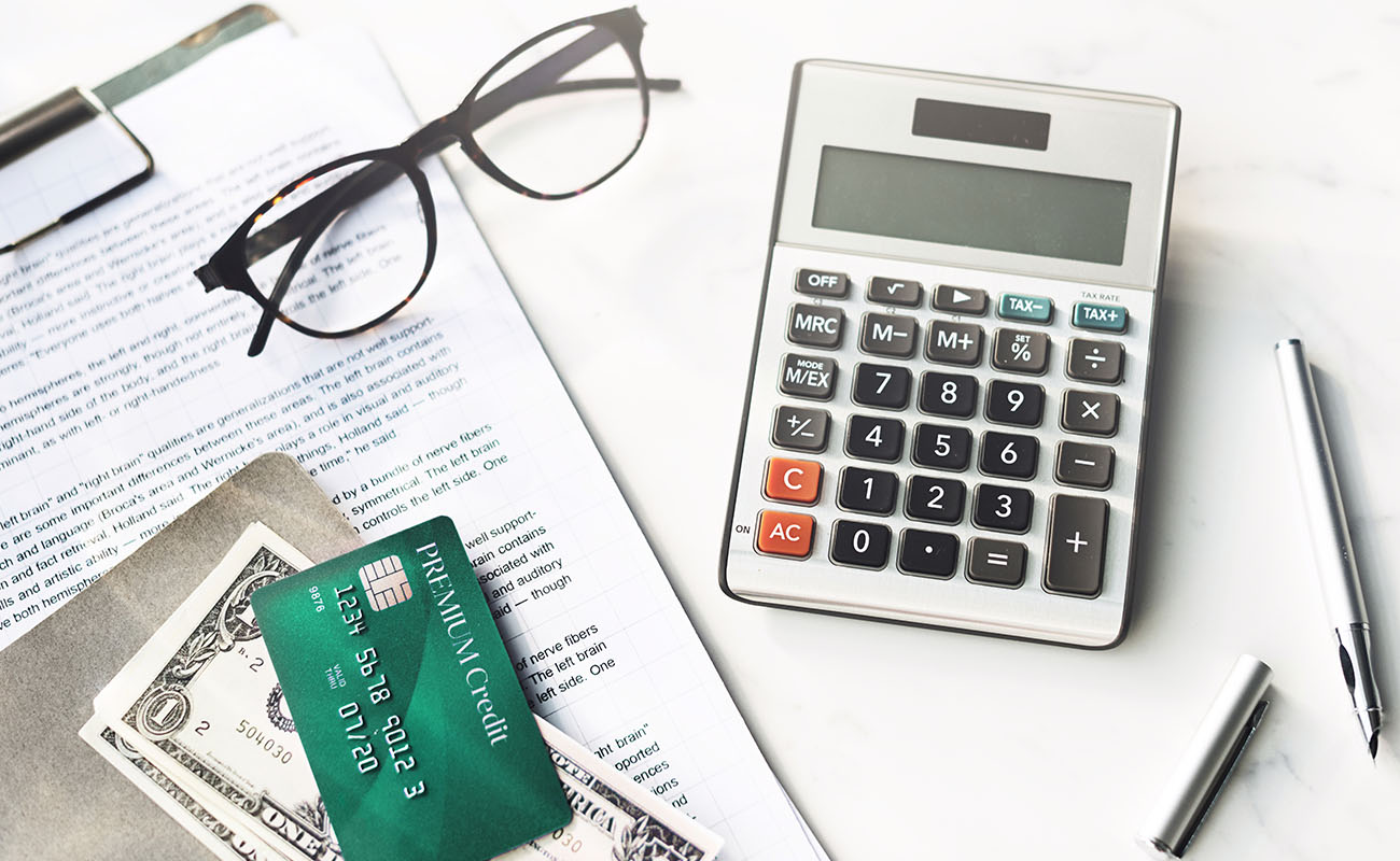 Calculator, money and credit card on money.