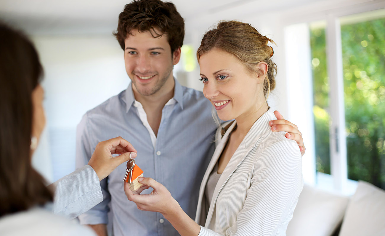 Couple talk to real estate agent.