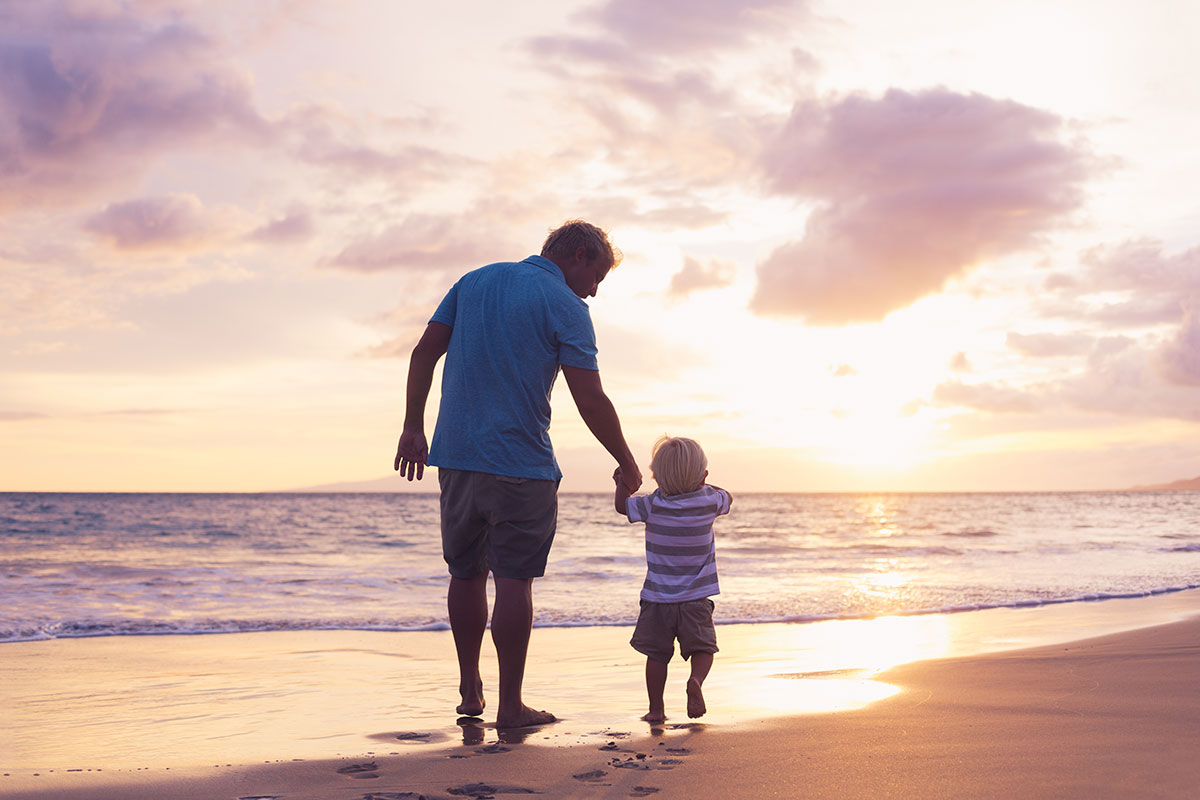 Father and Son Walk on a Beach.