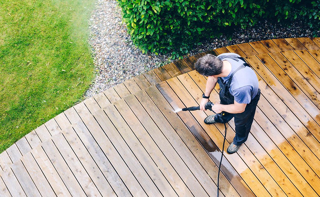 Man power washing deck.