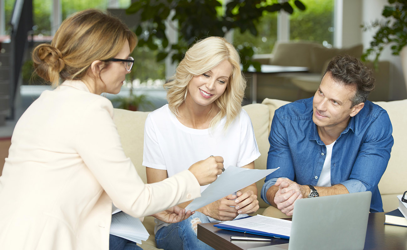 Real estate agent explaining costs to buyers.