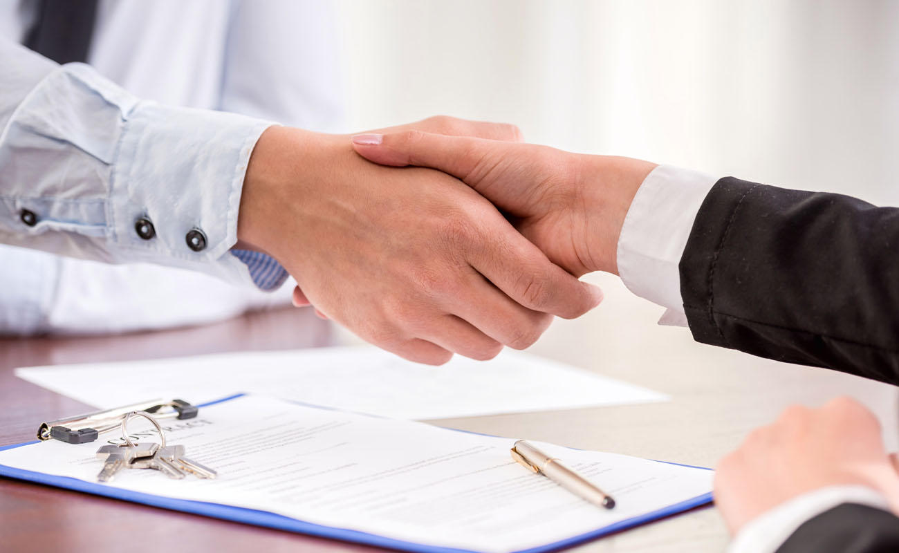 Shaking hands with contract in between.