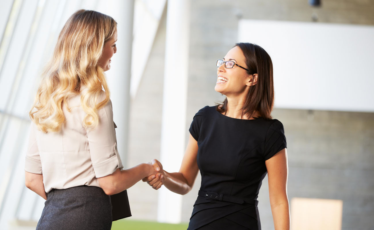Two businesswoman shaking hands.